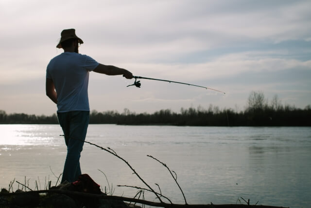 魚釣りをする男の画像